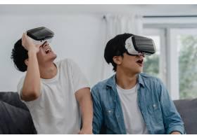年轻的亚洲同性恋情侣在家里用科技搞笑亚_6136993