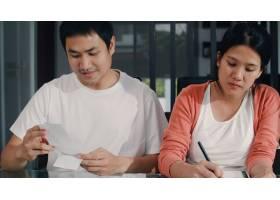 年轻的亚洲怀孕夫妇在家里记录收入和支出_6141950