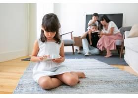 年轻女孩拿着智能手机坐在客厅的地板上玩游_9988631