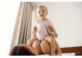 年轻快乐的母亲在家里的床上陪着她刚出生的_9321554