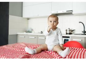 坐在厨房桌子上的可爱的小宝宝_9696743