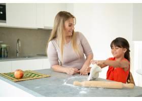 妈妈和女儿一起烘焙在厨房柜台上做面团_9650465
