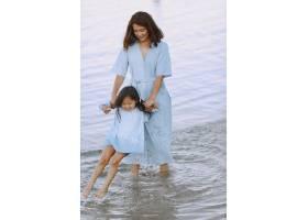 妈妈和女儿穿着一模一样的衣服一家人在河_10065301