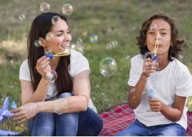 妈妈和孩子一起在户外做气球_9860909