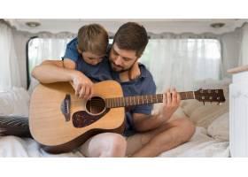 前景男子在大篷车里弹吉他紧挨着他的儿子_9943109