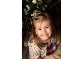 可爱的小女孩手里拿着一个玩具圣诞老人坐_9500347