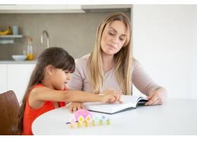 可爱的小女孩指着文字和妈妈一起学习_9988400