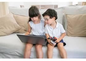 可爱的男孩和女孩坐在家里的沙发上用笔记_9988385
