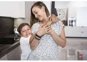 可爱的男孩在家里拥抱他的母亲_9423046