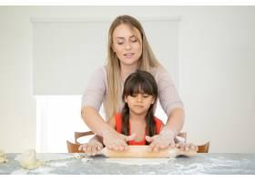 专心致志的女孩和她的妈妈用面粉在厨房桌子_9988444