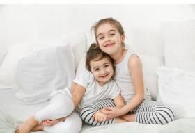 两个可爱的小女孩正依偎在卧室的床上家庭_10107402