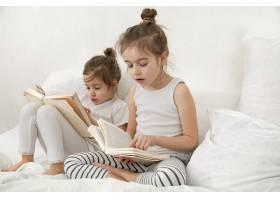 两个可爱的小女孩正在卧室的床上看书家庭_10107676