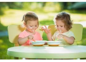 两个小女孩坐在一张桌子旁一起在绿色的草_9368670