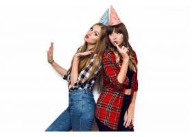 两个戴着派对帽的美女在白色墙上摆姿势的肖_9654792
