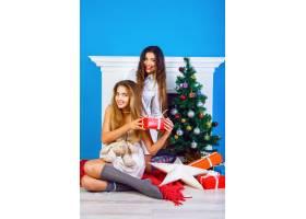 两个漂亮的闺蜜女孩在壁炉和装饰的新年树旁_9855759