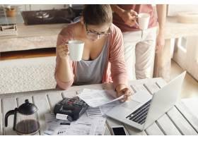 严肃的年轻女子戴眼镜管理家庭预算的顶视图_9957108