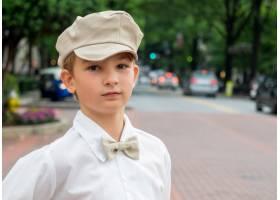 公园里一个打着蝴蝶结戴着帽子的小男孩的_9851477