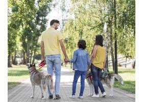 公园里带着孩子和狗的家庭在户外的后景_9860905