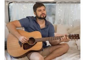 一个在大篷车里弹吉他的前视人_9943113