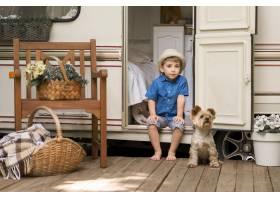一个小男孩坐在大篷车上旁边有一只可爱的_9942889
