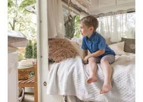 一个小男孩坐在大篷车里的坏东西上_9942891