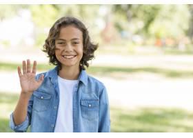 一个微笑的男孩在公园外面挥手_9860975
