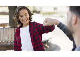 一个微笑的男孩在户外与他的父亲拳打脚踢_9860921