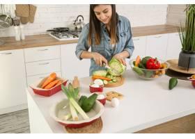 一位年轻漂亮的女士正在厨房准备各种蔬菜沙_9513361