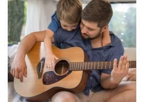 一名男子在大篷车里弹吉他紧挨着他的儿子_9943107