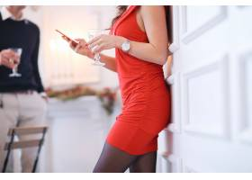 一名穿着红色连衣裙的女子拿着她的智能手机_9388705