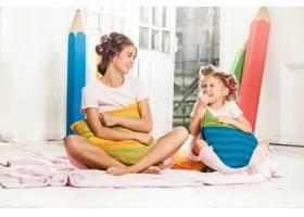 微笑的小女孩和她的母亲在白色上玩耍_10250521