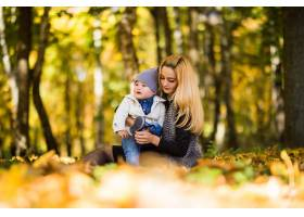 快乐的年轻母亲和她的小儿子在秋天的公园里_10121532