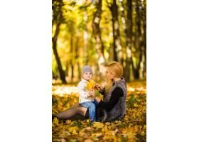 快乐的年轻母亲和她的小儿子在秋天的公园里_10121536