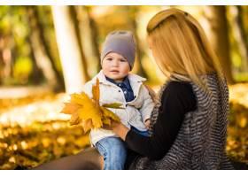 快乐的年轻母亲和她的小儿子在秋天的公园里_10121539