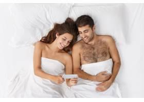 快乐的年轻男女睡前在床上放松看着手机屏_9879247