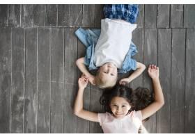 快乐的男孩和女孩躺在硬木地板上_3293735