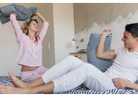 有趣的年轻情侣早上在床上玩得很开心玩着_9699634