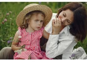 母亲带着女儿在夏日田野里玩耍_9658667