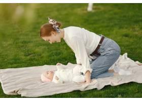 母亲带着她的婴儿在夏日花园里消磨时间_9343638
