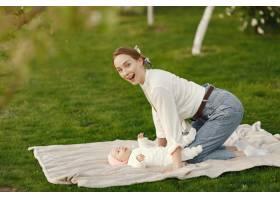 母亲带着她的婴儿在夏日花园里消磨时间_9343671