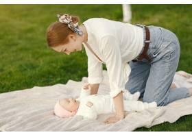 母亲带着她的婴儿在夏日花园里消磨时间_9343751