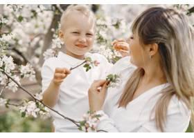母亲带着年幼的儿子在夏日的院子里玩耍_9344632