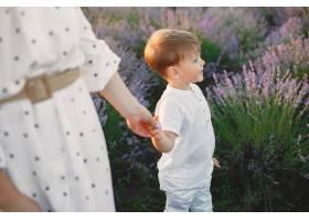 母亲带着年幼的儿子在薰衣草地里美丽的女_10062832