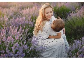 母亲带着年幼的儿子在薰衣草地里美丽的女_10062834