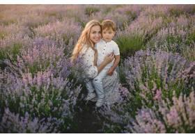 母亲带着年幼的儿子在薰衣草地里美丽的女_10062837