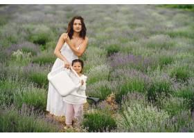 母亲带着年幼的女儿在薰衣草地里美丽的女_10065111