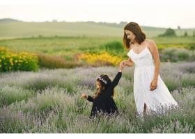 母亲带着年幼的女儿在薰衣草地里美丽的女_10065196