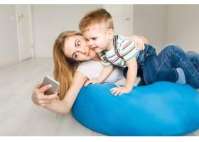 演播室拍摄了一位母亲抱着孩子在智能手机上_9860739