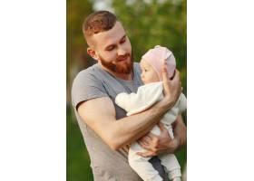 父亲带着她的孩子在夏日花园消磨时光_9343816