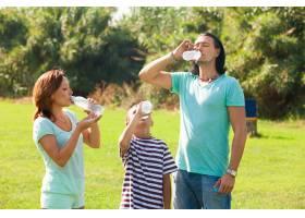 父母带着十几岁的孩子从瓶子里喝水_1329260